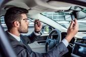 Fotografie side view of businessman wearing eyeglasses while sitting in car