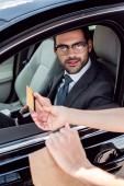 partial view of businessman in car giving credit card to waiter with take away food