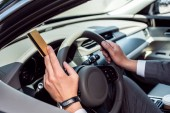 Fotografie partial view of businessman with credit card in hand sitting at steering wheel in car