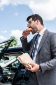 Fotografie side view of businessman eating take away doughnut while standing at car on street