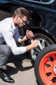 Photo concentrated young businessman in eyeglasses using wheel spanner for wheel replacement at street