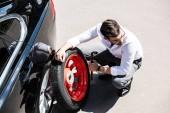 Fotografie pohled z vysoké úhlu mladého podnikatele výměna kola automobilu na ulici