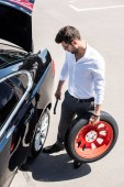 Fotografie pohled z vysokého úhlu mladé podnikatele v brýle drží klíč na kola a pneumatiky u auta na ulici