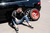 Fotografie Stylový unavený muž v sluneční brýle otřel čelo nástroje, pneumatiky a rozbité auto na ulici