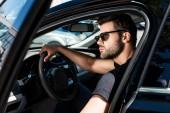 Photo serious stylish man in sunglasses closing door of his car at street
