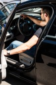Fotografie side view of stylish man in sunglasses closing door of his car at street