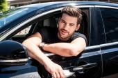 Photo portrait of smiling handsome young man sitting in his car