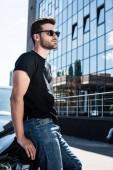 Fotografia vista laterale del giovane alla moda in occhiali da sole in piedi vicino alla sua automobile a street