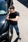 Photo high angle view of stylish young man in sunglasses checking wristwatch near his car at street