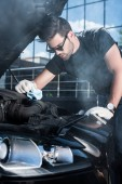 Fotografie young man in working gloves trying to repair engine of broken car with smoke coming out