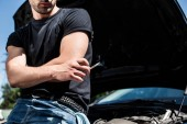 cropped image of man holding cigarette near broken car with opened bonnet at street