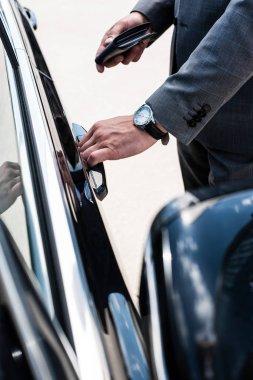 cropped shot of businessman opening car door