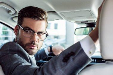 businessman in eyeglasses looking away while driving car