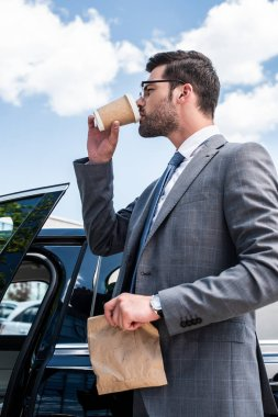 businessman in eyeglasses with take away food drinking coffee to go while standing near car on street