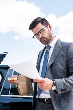 businessman with doughnut looking at documents while standing near car on street