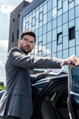 side view of confident businessman with papers in hands standing near car on street