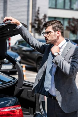 young businessman in eyeglasses closing car trunk at street