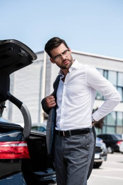 low angle view of handsome businessman taking off jacket and looking away near car