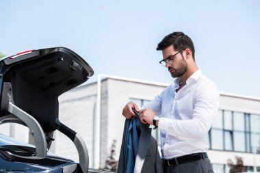 side view of businessman in eyeglasses putting jacket in car trunk at street