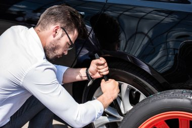 side view of focused young businessman in eyeglasses using wheel spanner for wheel replacement at street