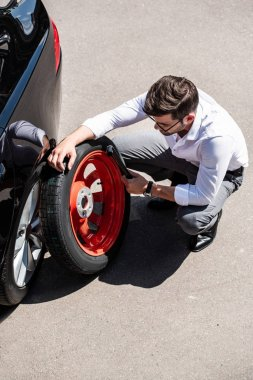 high angle view of businessman in eyeglasses holding tool for wheel replacement at street