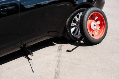 close up view of jack screw, wheel spanner and tire near broken car at street