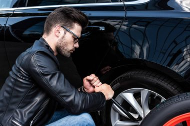 focused young man in sunglasses using wheel spanner for wheel replacement at street