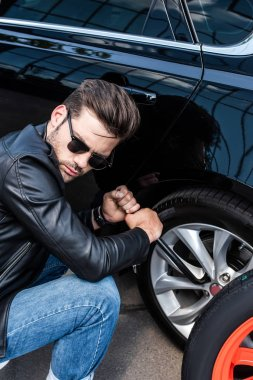 concentrated young man in sunglasses using wheel spanner for wheel replacement at street
