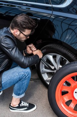 high angle view of young man in sunglasses using wheel spanner for wheel replacement at street