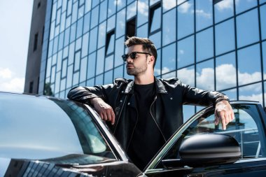 young stylish man in leather jacket and sunglasses looking away near car at street