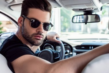 portrait of serious stylish man in sunglasses looking back while driving car