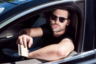 serious young man in sunglasses giving credit card while sitting in his car