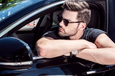 portrait of serious stylish man in sunglasses looking away while sitting in his car
