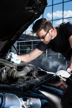 handsome young man in working gloves holding rag and looking at engine of broken car with smoke coming out