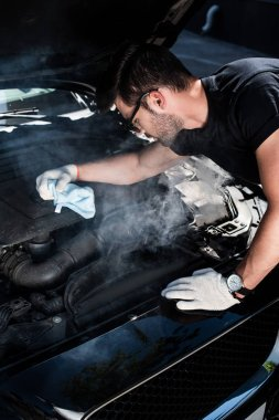 side view of young man in working gloves holding rag and looking at engine of broken car with smoke coming out