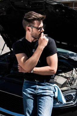 side view of stylish man in sunglasses smoking cigarette near car with opened bonnet