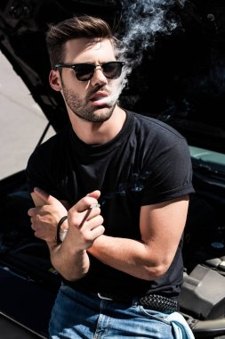 young stylish man in sunglasses smoking cigarette while standing near broken car with opened bonnet