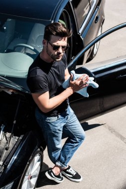 high angle view of young man in sunglasses wiping hands by rag near car with opened bonnet