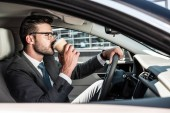 Fotografia side view of businessman in eyeglasses drinking coffee and riding car