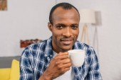 Fotografie young african american man holding coffee cup and smiling at camera
