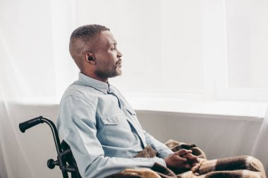side view of senior african american man sitting in wheelchair and looking away