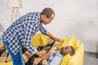 adult son covering senior father with plaid at home