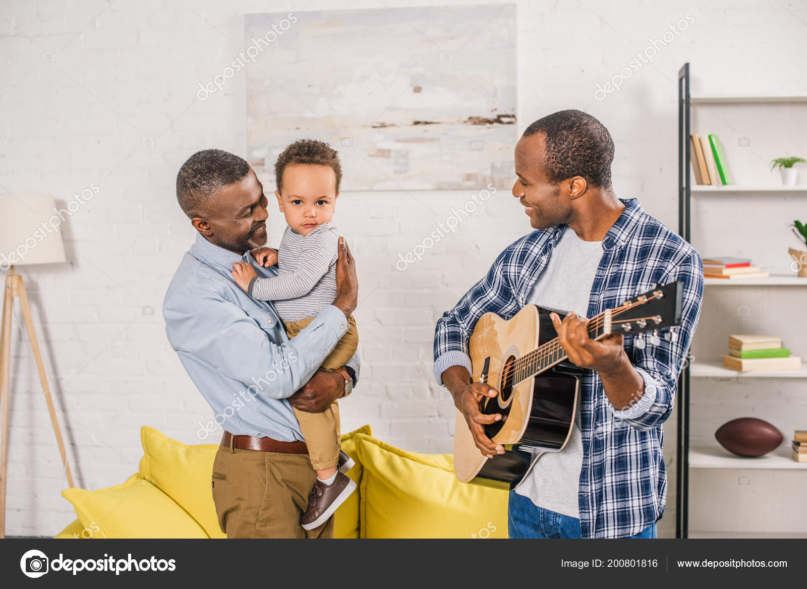 Smiling Young Man Playing Guitar Looking Happy Grandfather