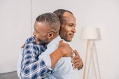 Photo happy senior father and smiling adult son hugging at home