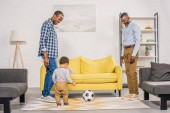 happy african american father, grandfather and little son playing with soccer ball at home