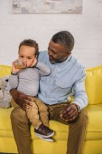 Fotografie happy african american grandfather looking at little grandson drinking from baby bottle at home