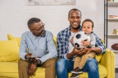 Fotografie happy senior man holding remote controller and looking at smiling young father and son sitting on sofa with soccer ball