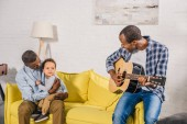 smiling young man playing guitar and looking at happy grandfather and grandson at home