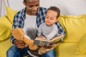 Fotografie cropped shot of smiling father holding teddy bear and reading book to little son