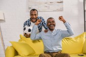Fényképek izgatott apa és fia, diadalmaskodott, és mosolyogva kamera focilabdával